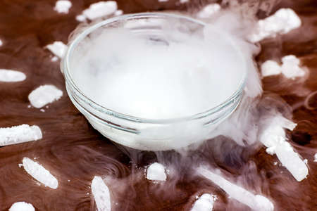 White cool dry ice (frozen carbon dioxide) with smoke effect in the glass bowl on the dark brown wooden background. Foto de archivo