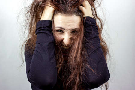 Stressed, frightened and screaming young mad woman in black against light background.
