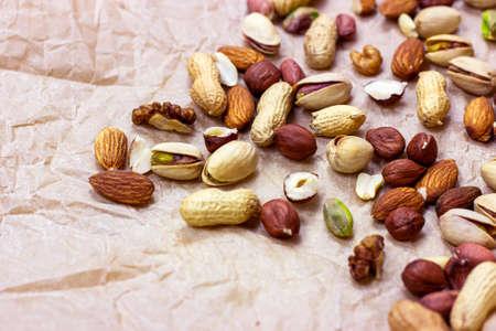 Different nuts: almonds, pistachios, peanuts, hazelnuts heap on light background.