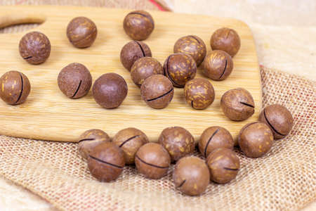 Brown macadamia nuts with wooden cutting board on light textile background.