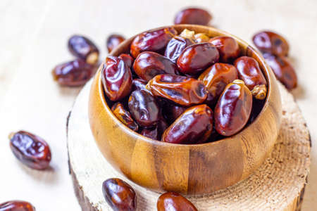 Sweet dried dates in round wooden bowl on light background in the kitchen.