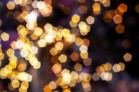 Blurred golden lights abstract background in the night, defocused dark glowing bokeh backdrop, magical yellow illuminated sparkle pattern.