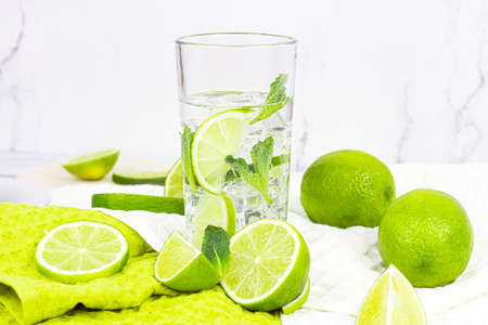 Fresh homemade mojito cocktail drink made from limes and mint leaves in a glass with ice cubes on light background in the kitchen.