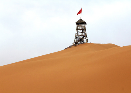 watchtower: watchtower with red flag in the desert in Shapotou, Ningxia province, China