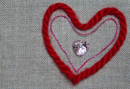 Heart of red and pink thread and shiny buttons in the shape of heart photo