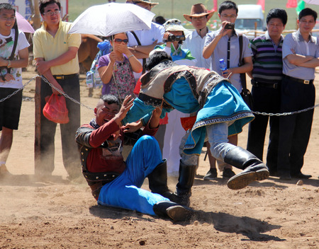 catch wrestling: INNER MONGOLIA, CHINA - JULY 14  The Mongolian young men wrestling in the in the steppe near Hohhot , Inner Mongolia on July 14, 2011, Wrestling is the most important of the Mongolian culture