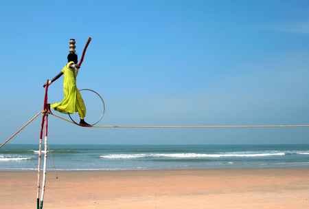 GOA, INDIA - FEB 12  Wandering indian tightrope walker playing on the beach of Goa, on Feb 12, 2008  Small groups of buskers traveling along the coast and often arrange free shows for tourists on the beach