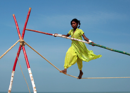 GOA, INDIA - FEB 12  Wandering indian tightrope walker playing on the beach of Goa, on Feb 12, 2008  Small groups of buskers traveling along the coast and arrange free shows for tourists on the beach
