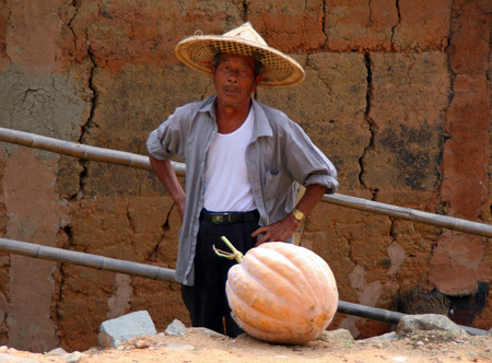 national fruit of china: YONGDING, CHINA - OCT 21, 2009  Elderly man in a straw hat, typical representative of the ethnic Hakka  Hakka is a large ethnic group that inhabiting mainly the southern provinces of China