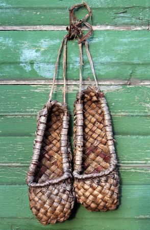Old bast shoes (traditional russian footwear) on a green wooden background Stock Photo