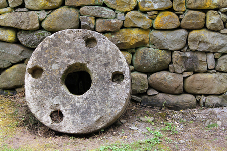 gristmill: Old millstone on a background of stone wall, Etara, Bulgaria