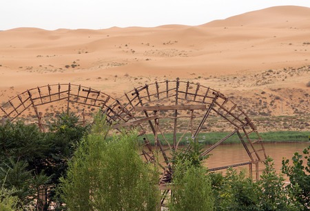 Ancient waterwheels on a background of desert and Yellow River, Shapotou Tourism area, Ningxia, China