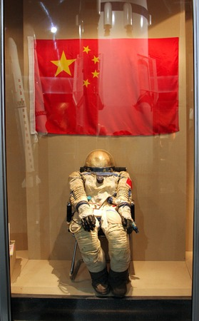 outer clothing: HOHHOT, INNER MONGOLIA - JUL 12, 2011: Astronaut space suit on a background of Chinese flag in the Inner Mongolia Museum. In 2003, China became the third space power Editorial