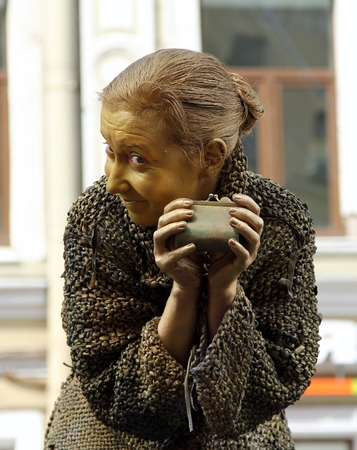 St. PETERSBURG, RUSSIA - JUL 5, 2014: Street actress (living statue) in the image of a greedy old woman from famous novel by Fyodor Dostoevsky, Crime and Punishment Editorial