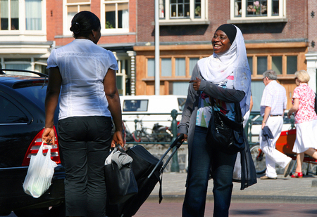 AMSTERDAM, NETHERLANDS - JUL 4, 2009: Two smiling African black women speaking on the street. Amsterdam is one of the most multicultural capitals Europe, is home to 200 different nationalities Editorial