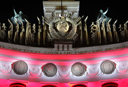MOSCOW, RUSSIA - AUG 23, 2014: Emblem of USSR and four (of fifteen) republics in festive lighting - architectural detail of facade of pavilion at All Russian Exhibition center Editorial