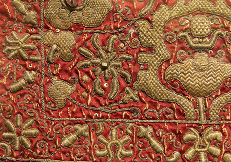 Vintage hand embroidery - golden floral pattern on red background