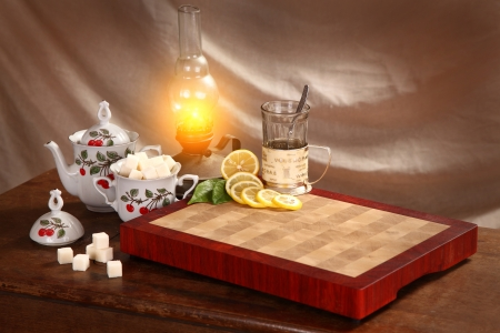 Black tea in a glass mug, an oil lamp a lemon and refined sugar on a wooden board photo