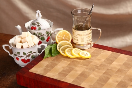 Black tea in a glass mug, a lemon and sugar on a wooden board Stock Photo - 21743438