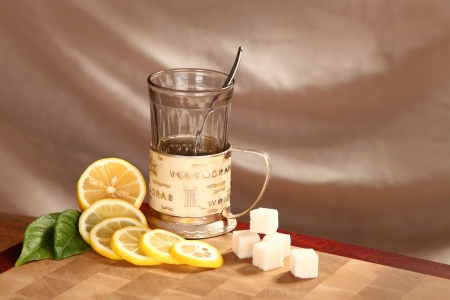 Black tea in a glass mug, a lemon and refined sugar on a wooden board Stock Photo - 21743444