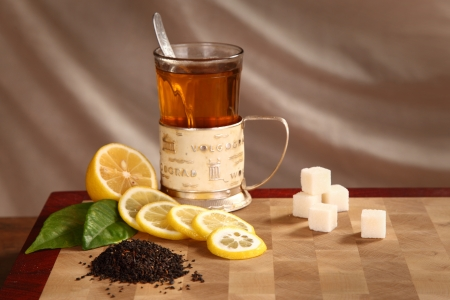 Black tea in a glass mug, tea leaves, a lemon and refined sugar on a wooden board Stock Photo - 21743445