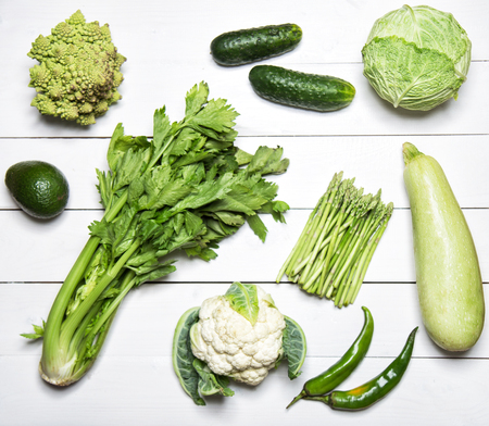 kinds: Different kinds of green vegetables on white wooden table. Top view Stock Photo