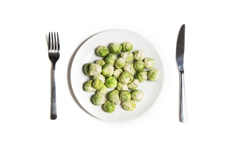 Diet vegetarian food isolated on white top view. Baby brussels sprouts on a plate with fork and knife Stock Photo