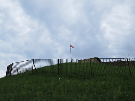 Polish Flag in Wind on a Tower of Stronghold with Clouds in the Background Archivio Fotografico