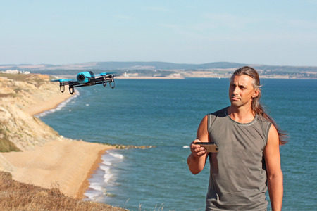 Man with the controlled drone on the cliff on the beach