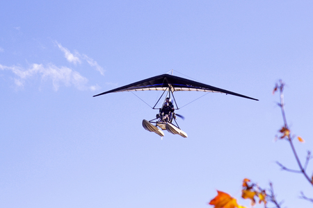 Motorized hang glider flying in the blue  cloudy sky in autumn time Stock Photo