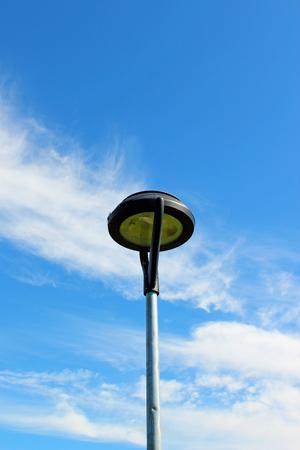 Street lantern isolated on the blue cloudy sky