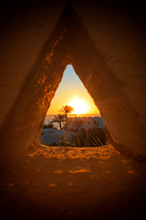 View of the sunset through a triangular hole in Sharm-el-Sheikh, Egypt.