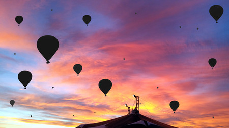 Black silhouettes of the hot air balloons over the circus tent on a colorful sunset background Stock Photo