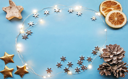 Christmas background with xmas decorations - chrismas sparkle lights in the centre of the blue canvas background. Dried lemon citrus slices ,pine cones, christmas stars in the corners. Merry christmas card. Banque d'images
