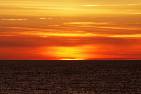 An abstract landscape with sunset over a slightly wavy surface of the sea 版權商用圖片