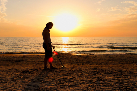 Man silhouette with metal detector on sunset on the beach