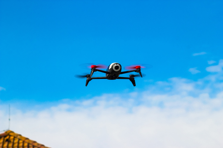 Drone flying overhead in cloudy blue sky over the roof of the house