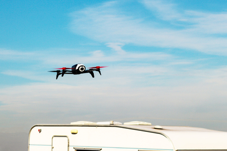 Flying drone with mounted camera over the white caravan