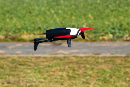 Flying drone with mounted camera in the park.