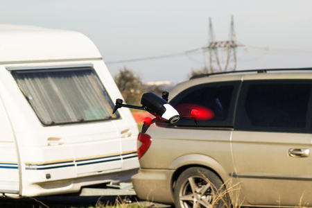 Flying drone with mounted camera fly near car with caravan