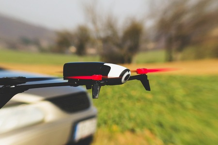 Flying drone overtake the car outdoor Stock Photo