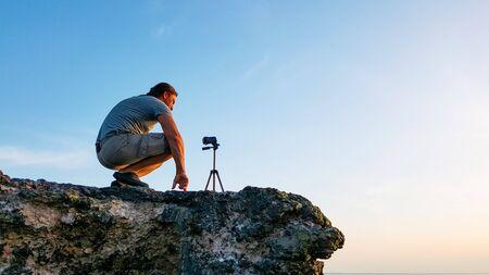Fotografo di viaggio uomo seduto sulla roccia e prendendo video della natura del bellissimo tramonto sulla spiaggia. Videografo professionista escursionista turistico in vacanza avventura riprese con videocamera su treppiede.