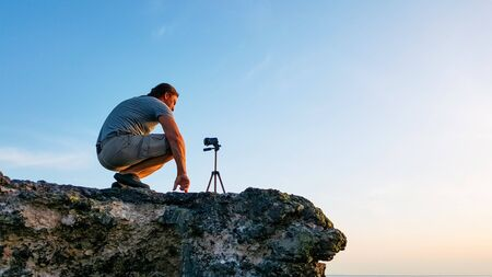 Hombre fotógrafo de viajes sentado en la roca y tomando videos de la naturaleza de la hermosa puesta de sol en la playa. Camarógrafo profesional de turismo excursionista en vacaciones de aventura filmando con cámara de video en trípode.