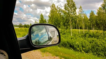 車のサイドビューミラーでキャンピングカーバン反射。車輪の上の生活。田舎の景色の背景 - 緑の森と曇りの青空。旅行の概念。