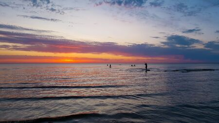 Stand up paddle board group of young people silhouettes paddle boarding on the sea during sunset. Summer vacation and sport concept.