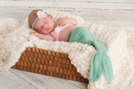 2 week old newborn baby girl wearing a crocheted turquoise and pink mermaid costume, sleeping in a basket with a bleached wood background   Stock Photo
