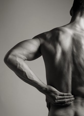 A black and white photo of a muscular man holding his lower back as if experiencing a backache   Stock Photo