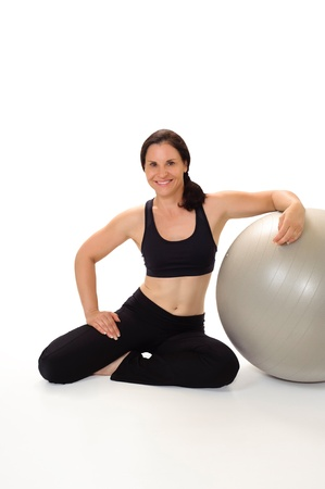physically: Portrait of a beautiful, physically fit woman in her 40s wearing workout clothing, smiling and leaning on an exercise ball  Shot in the studio and isolated on a white background  Stock Photo