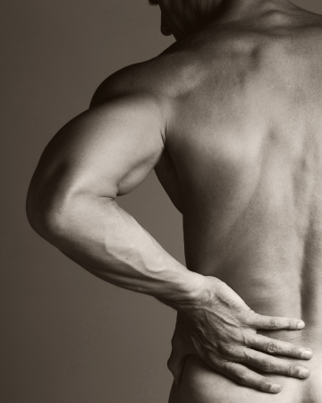 nude back: A black and white image of a muscular man holding his lower back as if experiencing a backache