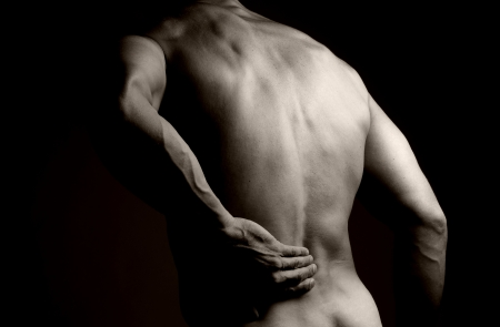 Black and white image of the back of a muscular man  He is rubbing his lower back as if to indicate a backache   Stock Photo